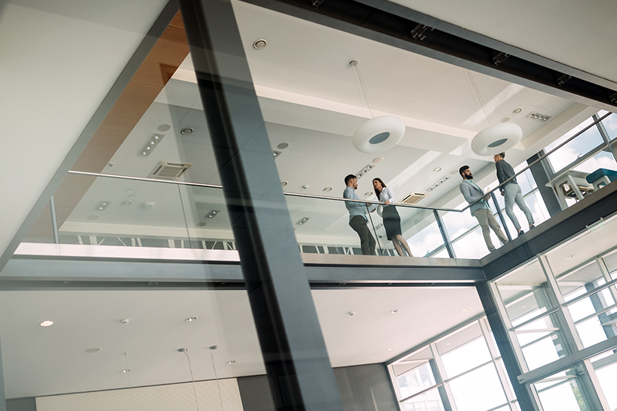 Business Insurance - Group of Business People Walking and Talking in the Background in a Large Modern Office Building
